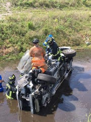 Palm Bay Fire Rescue works to extricate a driver trapped after his vehicle rolled over into a pond near I-95 Sunday.