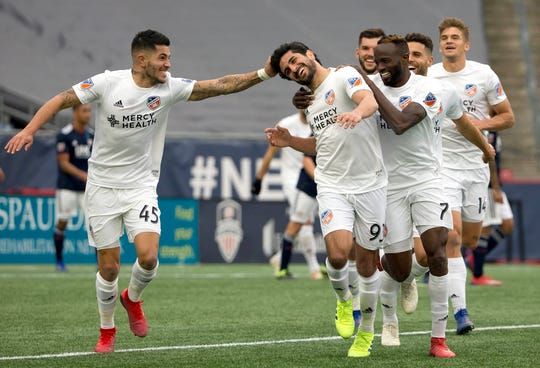 FC Cincinnati midfielder Kenny Saief (93) is congratulated after his goal by midfielder Emmanuel Ledesma (45) and forward Roland Lamah (7) during the second half of Cincinnati's 2-0 win over the New England Revolution at Gillette Stadium on March 24.