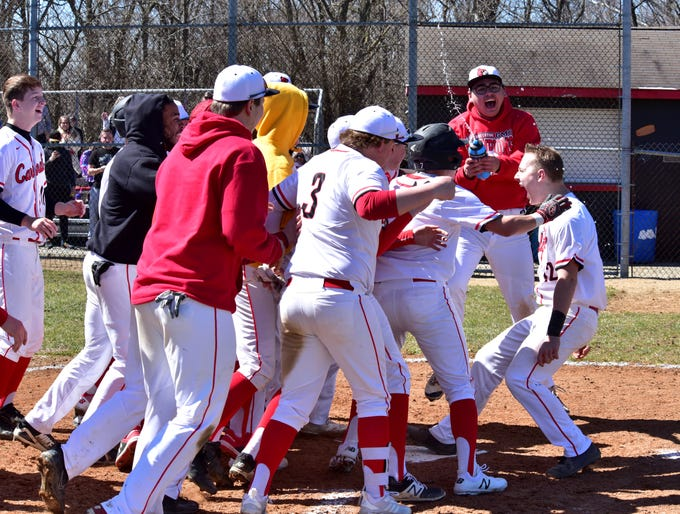 Luke Murray (right) steps on home plate with jubilation and team celebration after belting a solo, walk off home run to lift Colerain to an opening day victory at Colerain High School, March 23, 2019.