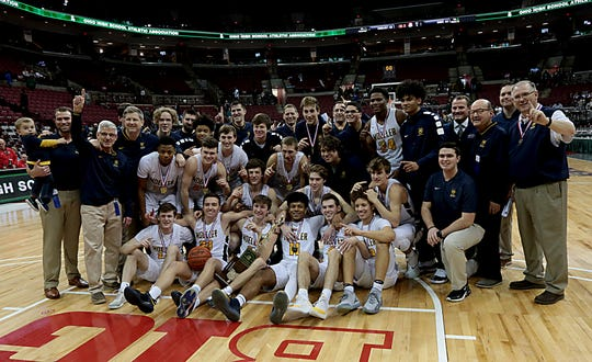 Moeller celebrates with the state championship trophy after defeating St. Vincent-St. Mary at the Schottenstein Center in Columbus Saturday, March 23, 2019.