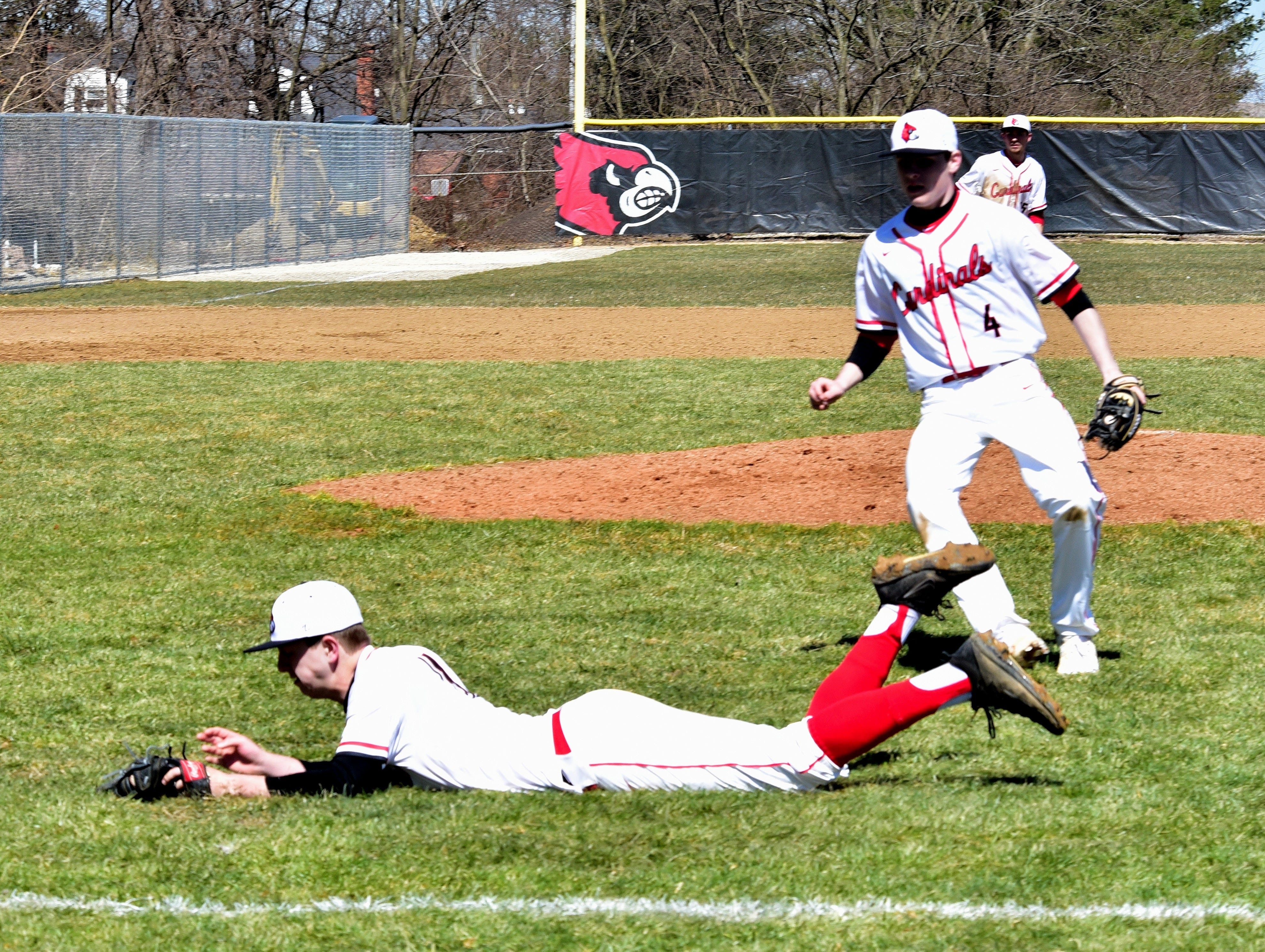 Cameron Foster of Colerain hits the ground but keeps the ball secured in his glove to put out a Springboro player on a bunt attempt turned pop-up at Colerain High School, March 23, 2019.