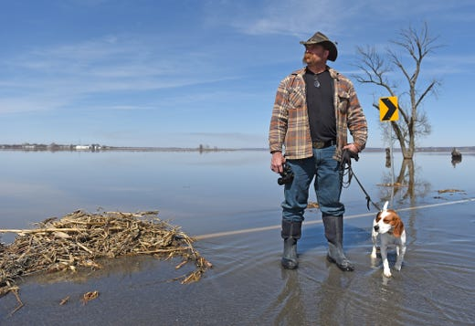 Larry Pace, an Omaha firefighter, poses for a portrait at the edge of a flooded road near Sidney with his dog Duke as he looks toward his home on Friday, March 22, 2019. Pace slept in his truck the first four days after the flood as he waited for the waters to recede so he could return home.