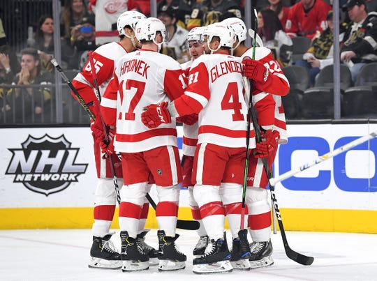 Detroit Red Wing players come together to celebrate a goal scored by Detroit Red Wings center Luke Glendening (41) during the first period at T-Mobile Arena on Saturday, March 23, 2019.