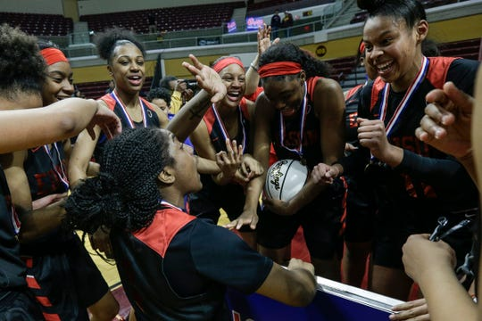 Detroit Edison players celebrate their back-to-back-to-back championship after the Pioneers defeated Freeland 77-58 at the MHSAA girls Division 2 final at Van Noord Arena in Grand Rapids, Saturday, March 23, 2019.