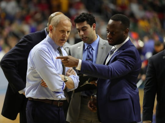 Michigan coach John Beilein talks to assistant Chinedu Nwachukwu during a break in the action against Florida in the NCAA tournament Saturday, March 23, 2019 at Wells Fargo Arena in Des Moines, Iowa.