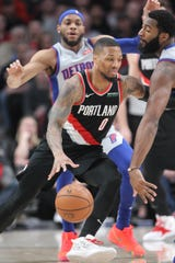 Portland Trail Blazers guard Damian Lillard dribbles around Detroit Pistons center Andre Drummond in the first half at Moda Center, March 23, 2019.