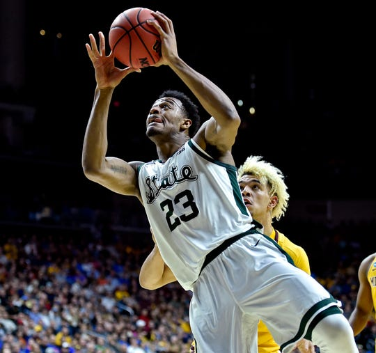 Michigan State forward Xavier Tillman shoots the ball against Minnesota forward Jarvis Omersa during the first half in the second round of the NCAA tournament at Wells Fargo Arena on Saturday, March 23, 2019.