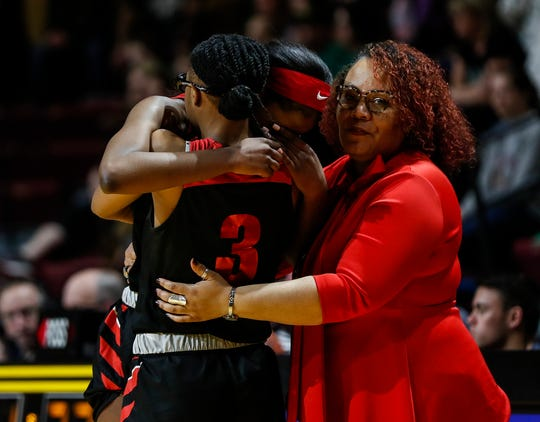 Detroit Edison guard Rickea Jackson (5) is comforted by teammate guard Gabrielle Elliott (3) and assistant coach Sharleta Paris in the last seconds of the second half of MHSAA girls Division 2 final against Freeland at Van Noord Arena in Grand Rapids, Saturday, March 23, 2019.