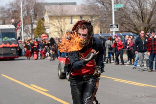 Fire performer Shadowe Daiz performs during the 10th annual Marche du Nain Rouge parade through Midtown Detroit on Sunday, March 24, 2019.