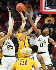 Michigan State forward Aaron Henry (11) and Michigan State forward Kenny Goins (25) converge on Minnesota guard Amir Coffey (5) in the second half.