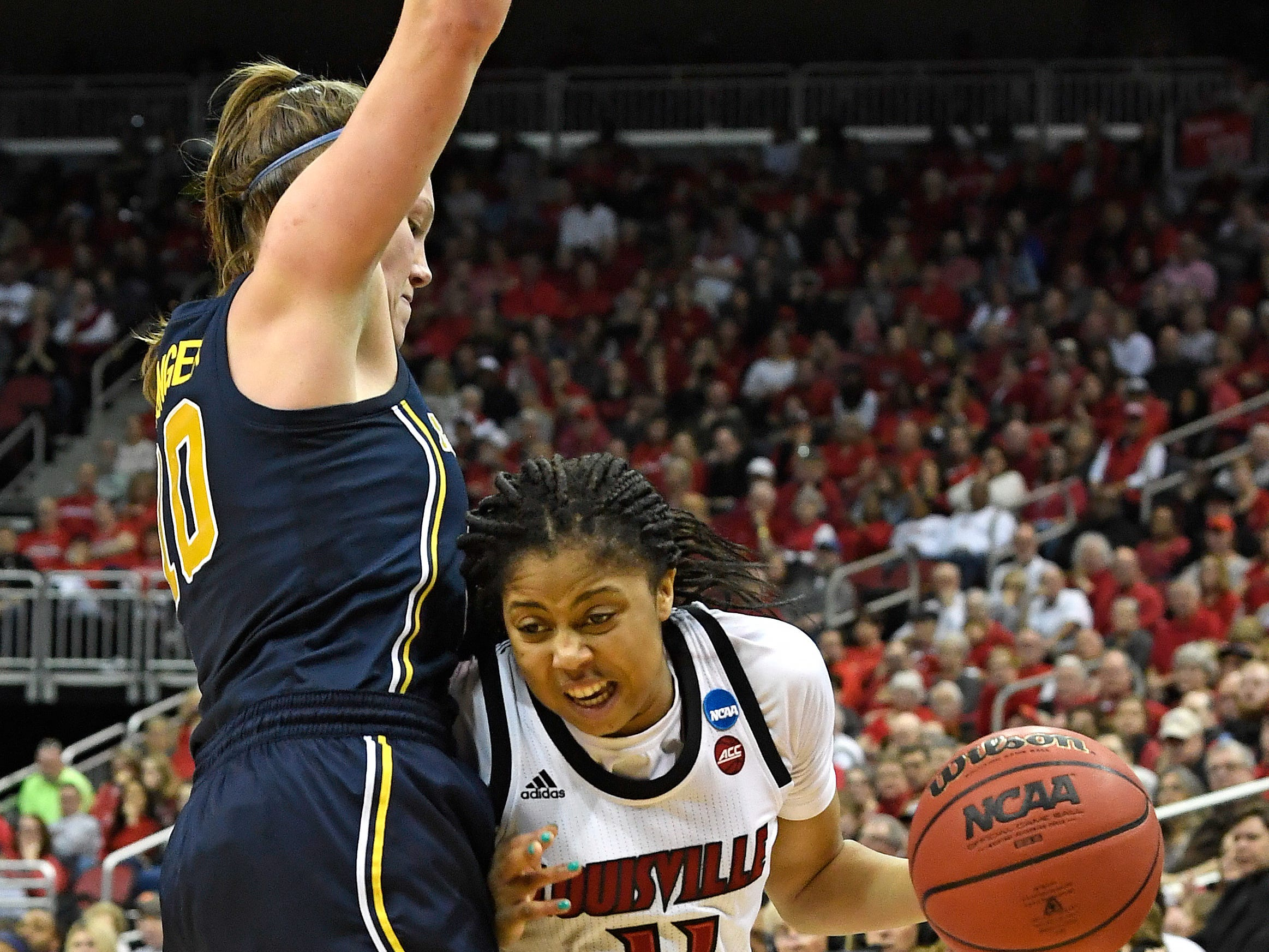 Louisville guard Arica Carter attempts to get around the defense of Michigan guard Nicole Munger.