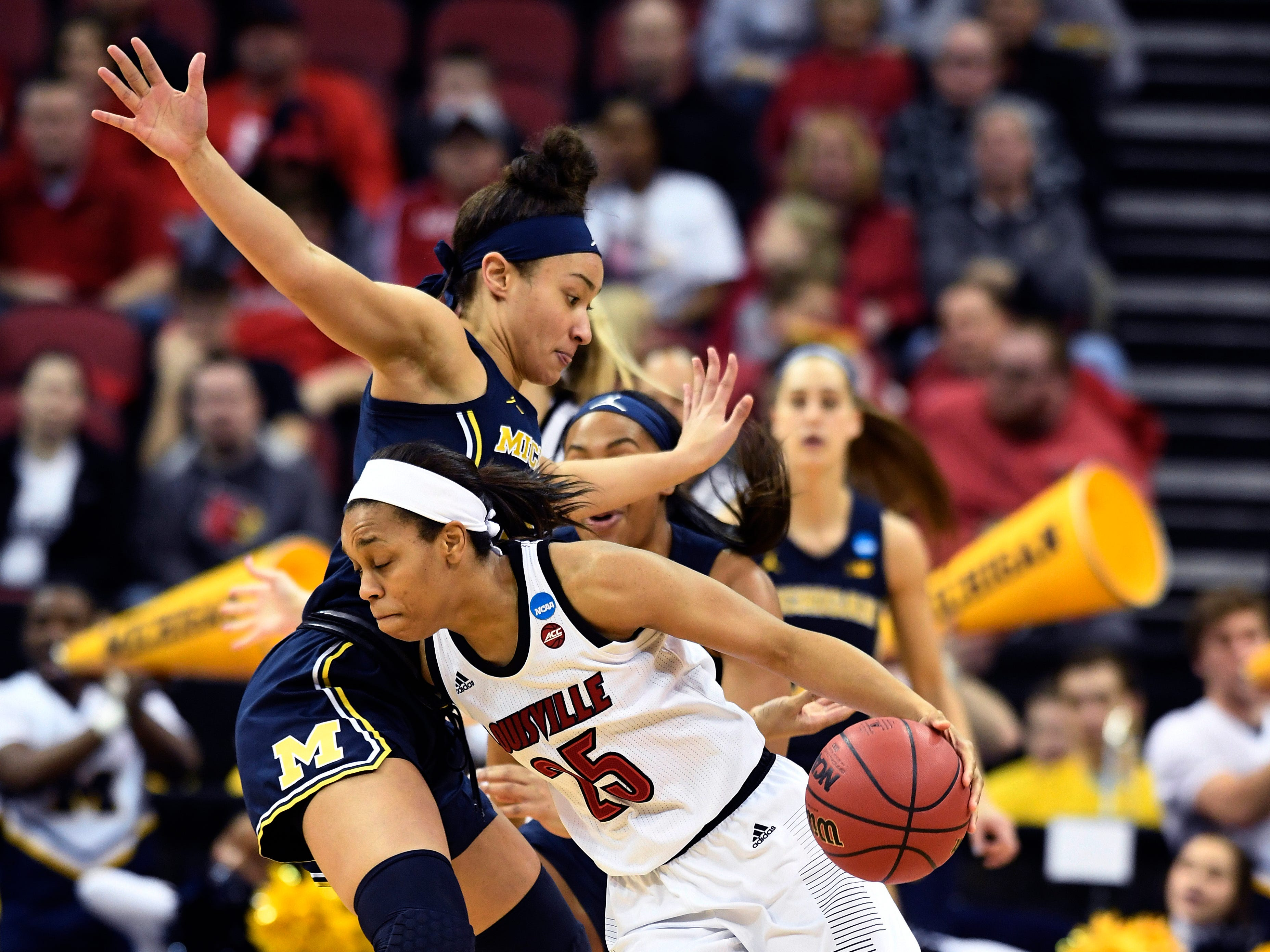 Louisville guard Asia Durr drives under the defense of Michigan forward Hailey Brown.