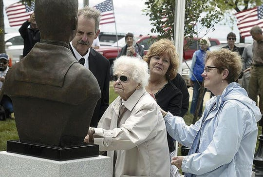 CORRECTS DATE - In this 2017 photo, Peg Ezdebski, surrounded by her children, looks at a bronze bust of her brother and Medal of Honor winner, William Charette, that was placed in the Veterans Memorial in Stearns Park, in Ludington, Mich. (Jeff Kiessel/Ludington Daily News via AP)
