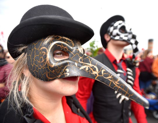 Anna Kotov, left, and her boyfriend, Mark Van Baak, both of Troy, wear masks with long noses as they are 'chasing The Nain,' before the march. XXXXThrongs of revelers participate in the Marche du Nain Rouge, Sunday, March 24, 2019, as they march South on Second Ave. at Canfield for eight blocks to the Masonic Temple near Cass Park. The Nain Rouge is a legendary hobgoblin creature whose appearance is believed to bring misfortune to Detroit. (Todd McInturf, The Detroit News)2019.