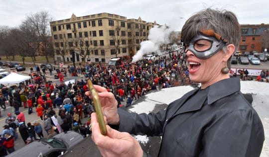Traffic Jam and Snug Restaurant co-owner Carolyn Howard, of Grosse Pointe Park, lets out a yell as she photographs revelers in front of her establishment before the march.