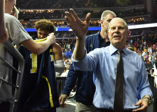 Michigan head coach John Beilein reacts with fans at the end of the game.