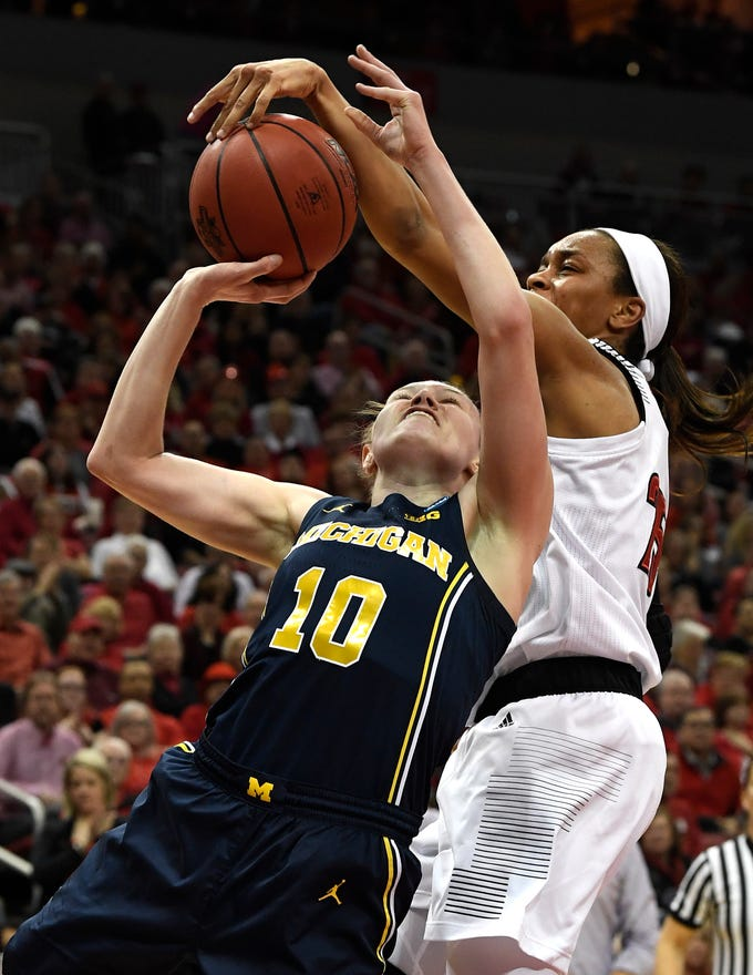 Louisville guard Asia Durr attempts to block the shot of Michigan guard Nicole Munger during the first half of a second-round game in the NCAA Tournament on Sunday, March 24, 2019, in Louisville, Ky.