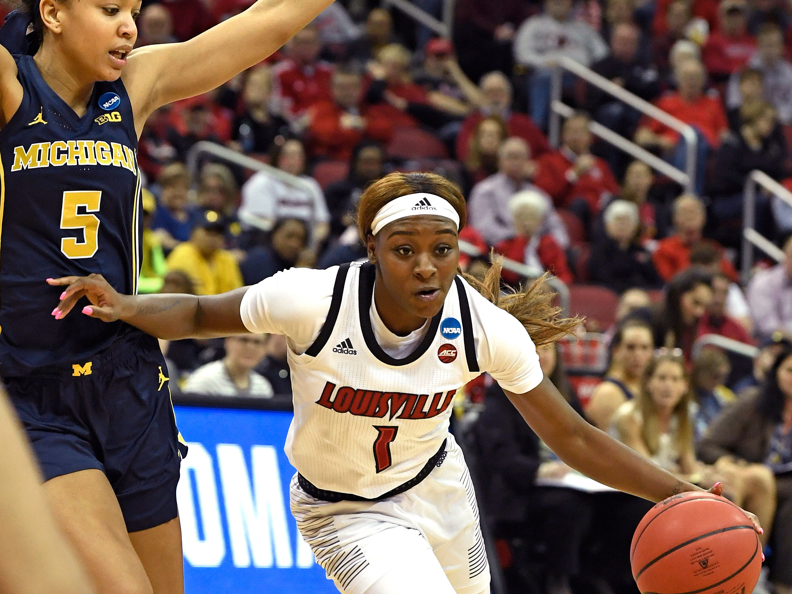 Louisville guard Dana Evans drives past the defense of Michigan forward Kayla Robbins.