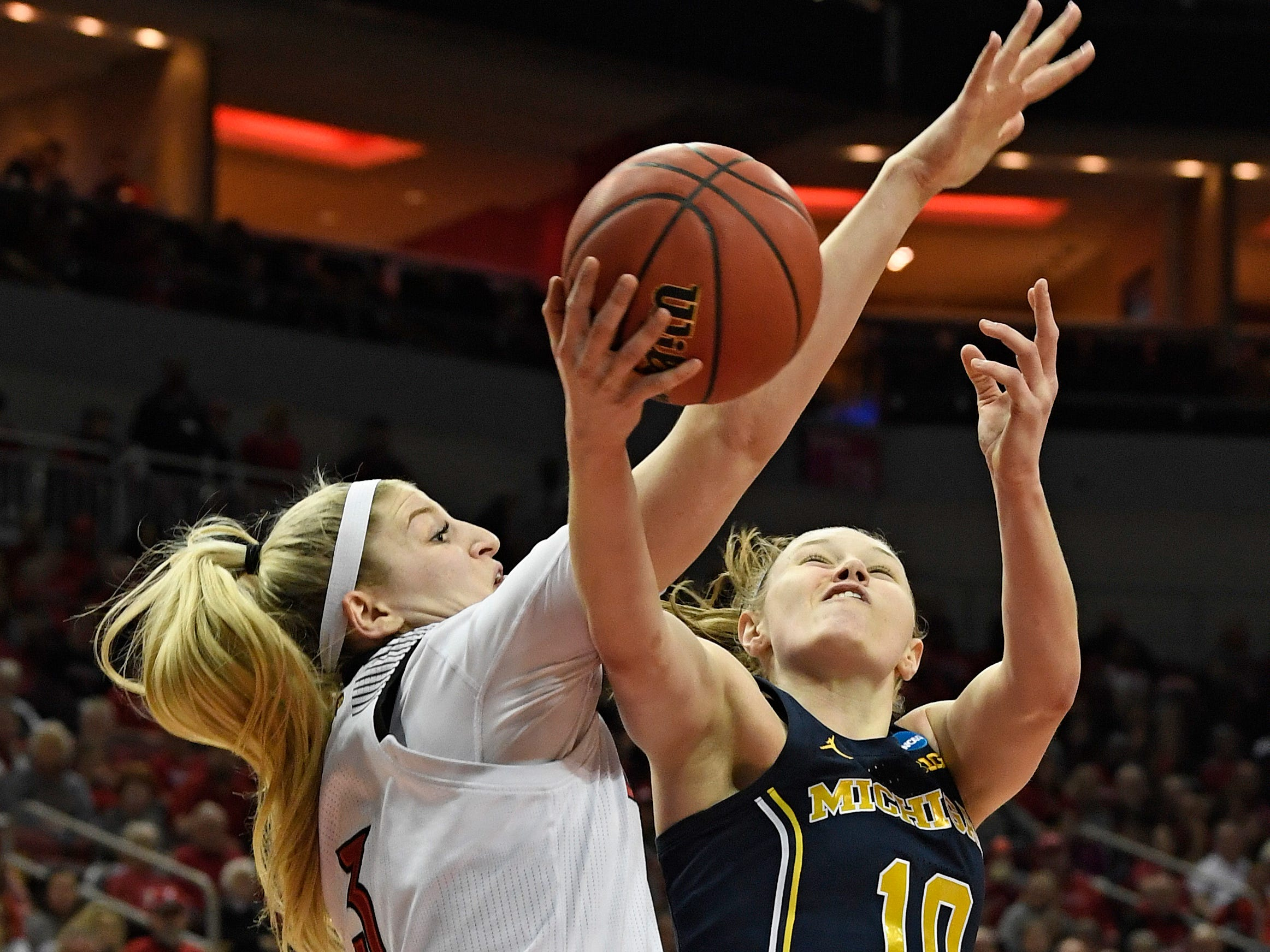 Michigan guard Nicole Munger is fouled by Louisville forward Sam Fuehring.