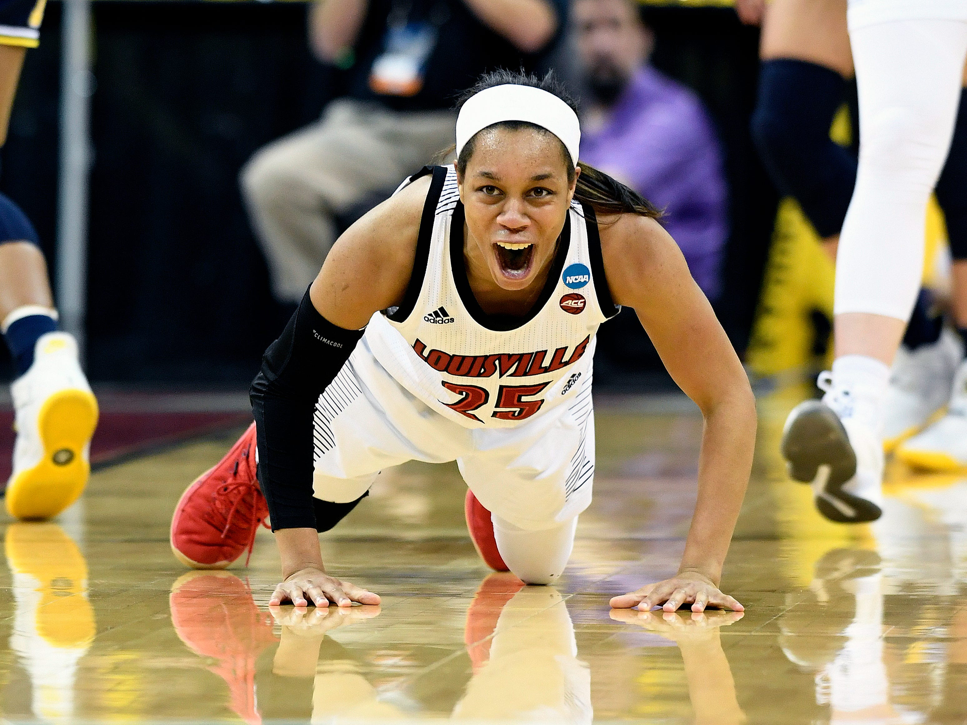 Louisville guard Asia Durr shouts as she gets off the floor after being fouled.
