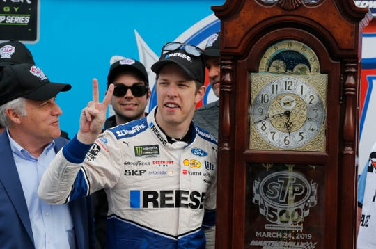 Brad Keselowski (2) celebrates with the trophy grandfather clock in Victory Lane after winning a NASCAR Cup Series auto race Sunday at Martinsville Speedway.
