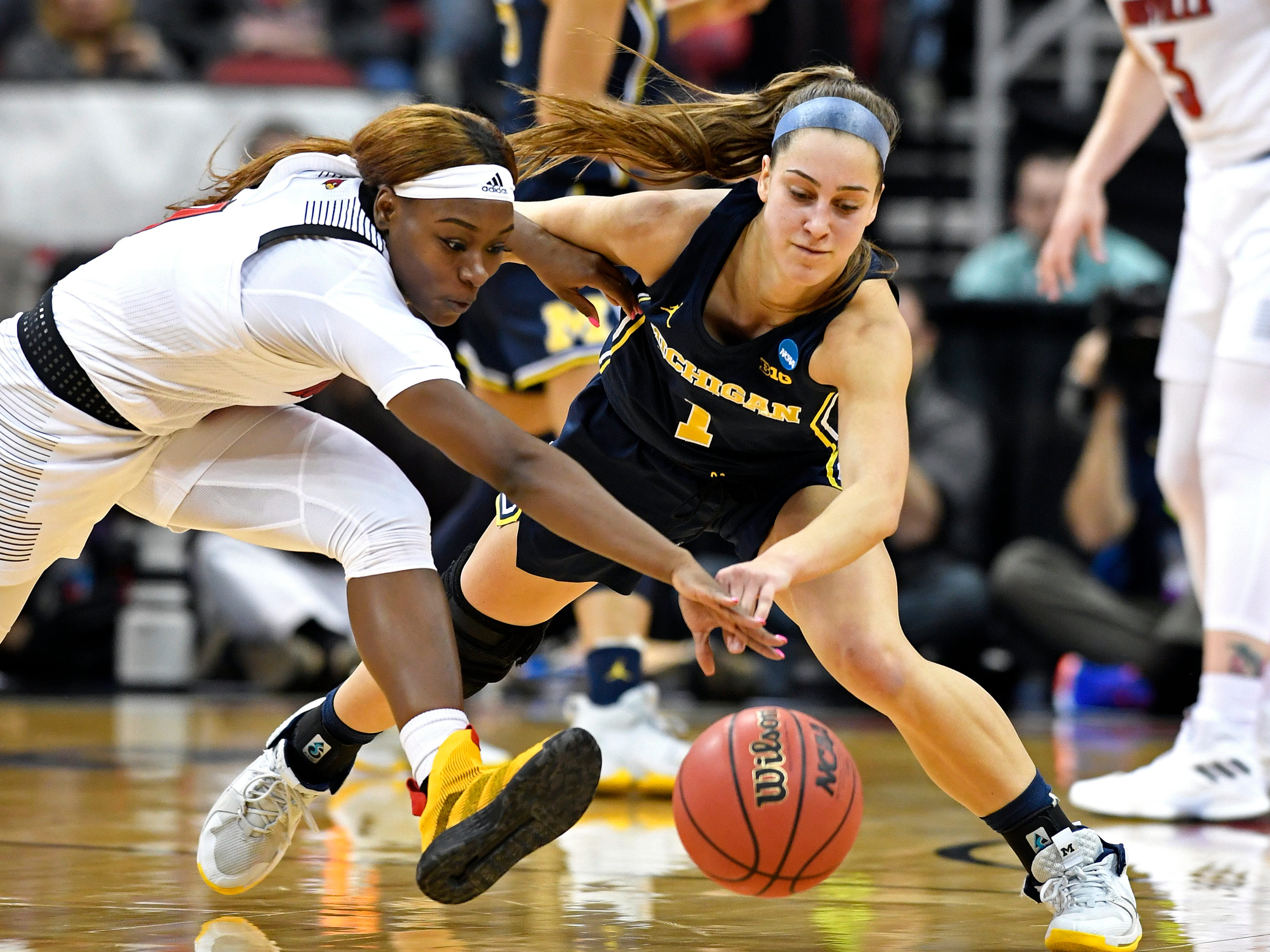 Louisville guard Dana Evans, left, battles Michigan guard Amy Dilk for the ball.