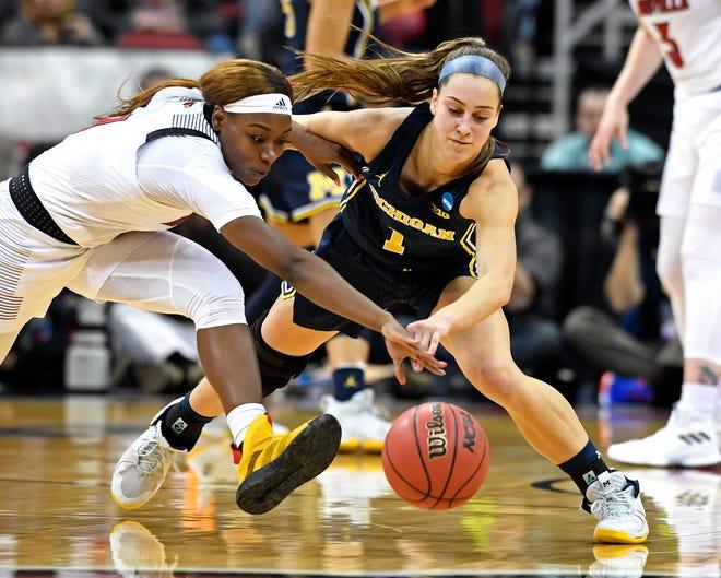 Louisville guard Dana Evans, left, battles Michigan guard Amy Dilk for the ball.