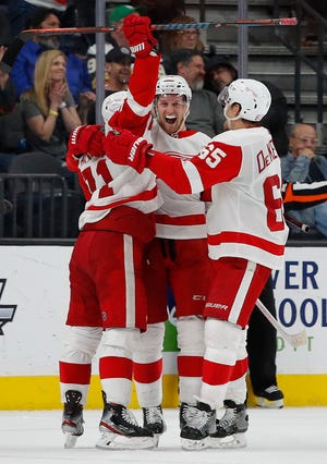 Detroit Red Wings celebrate after right wing Anthony Mantha, center, scored during overtime.