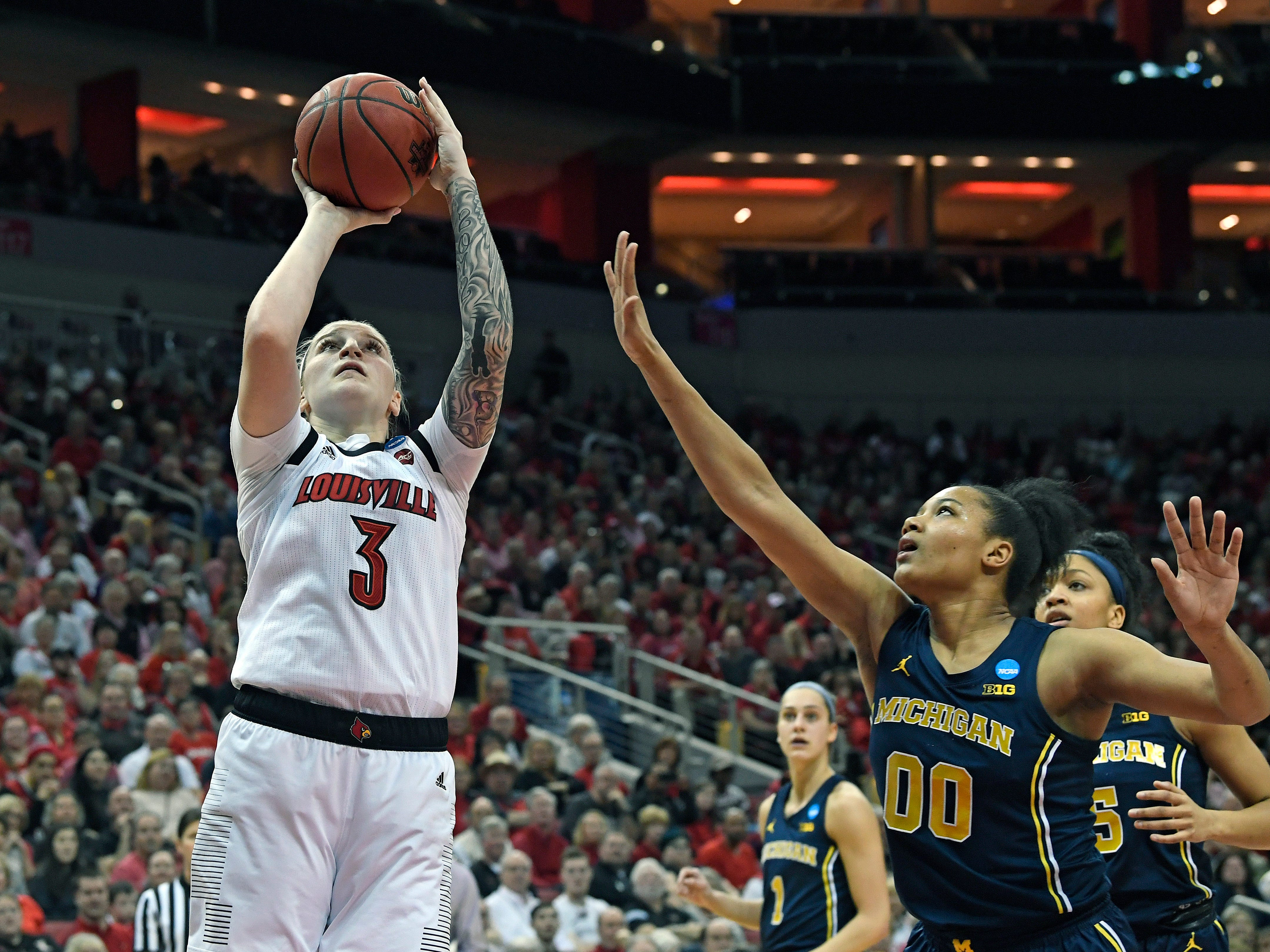 Louisville forward Sam Fuehring shoots over the defense of Michigan forward Naz Hillmon.