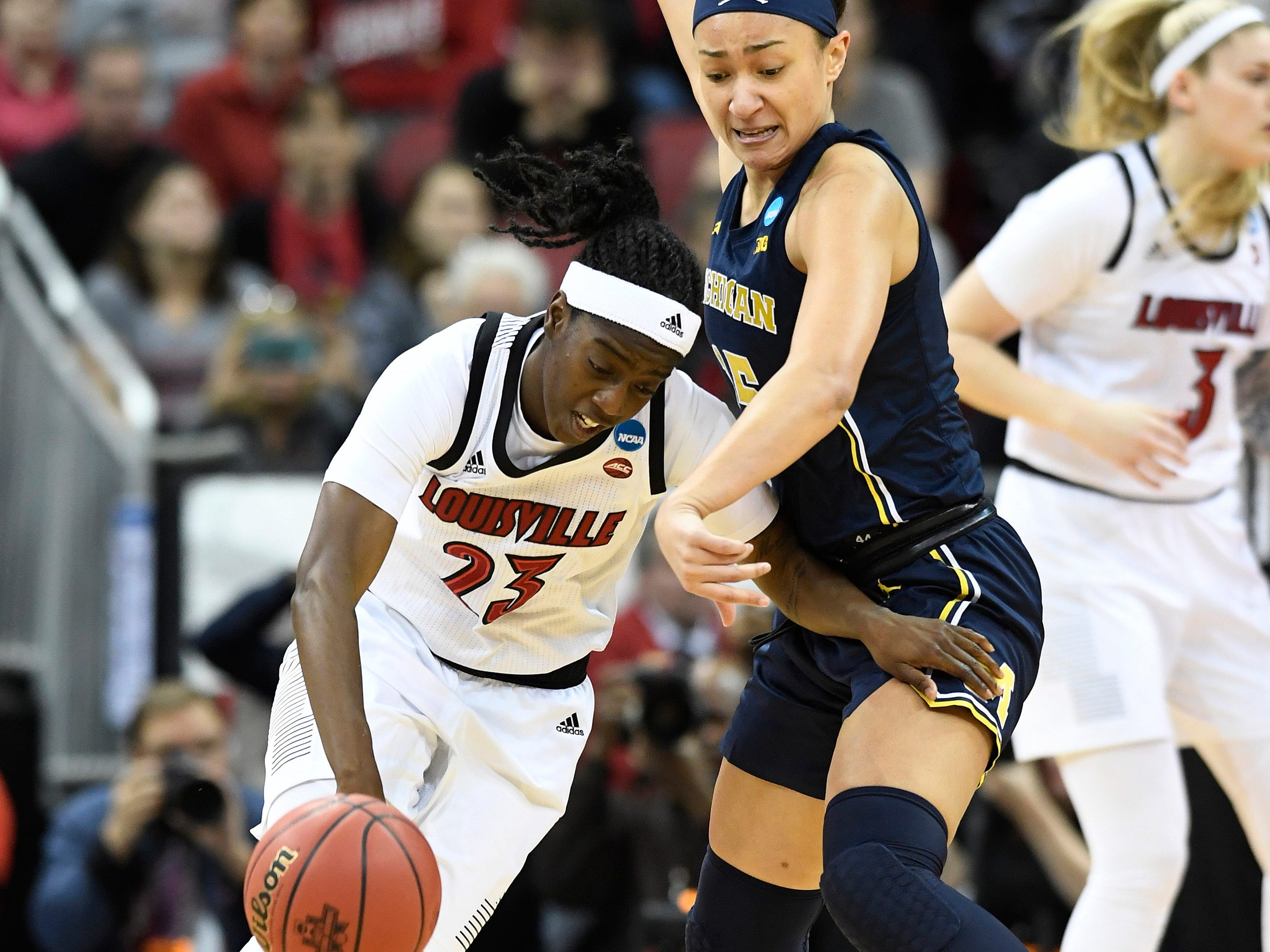 Louisville guard Jazmine Jones tries to get past the defense of Michigan forward Hailey Brown.