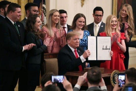 President Donald Trump signs an executive order protecting free speech on college campuses amid Young Americans for Freedom members.