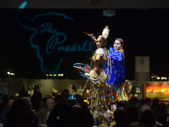 Dani Hardesty, left, dances a medicine dance and Mailey Yazzie dances a fancy dance before The Russell Live Auction on Saturday night in the Great Falls Civic Auditorium.