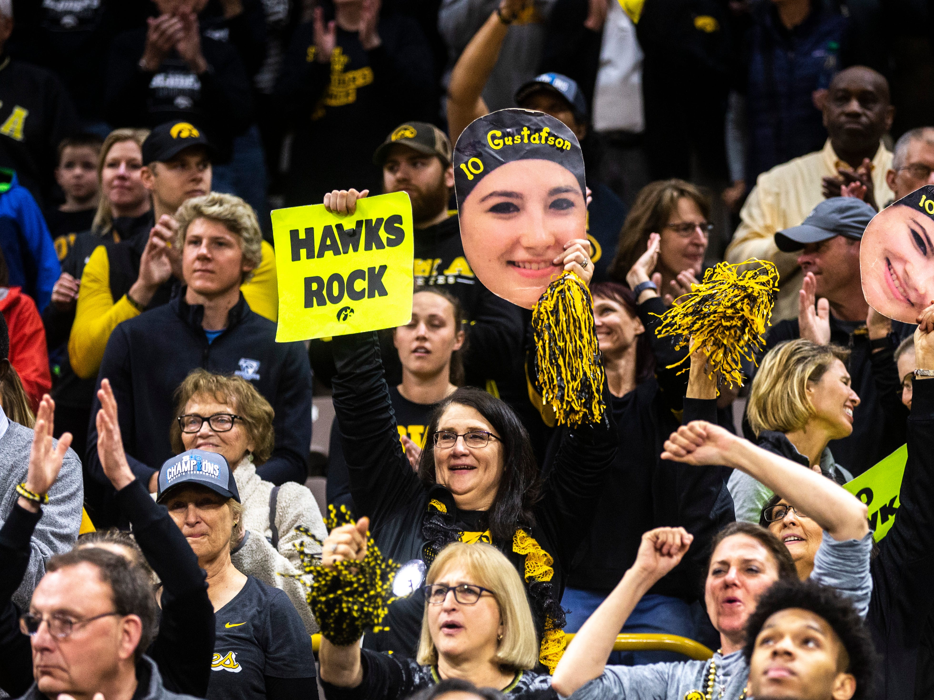 Iowa Hawkeye fans hold up cutouts of Iowa center Megan Gustafson's head during a NCAA women's basketball tournament second-round game, Sunday, March 24, 2019, at Carver-Hawkeye Arena in Iowa City, Iowa.