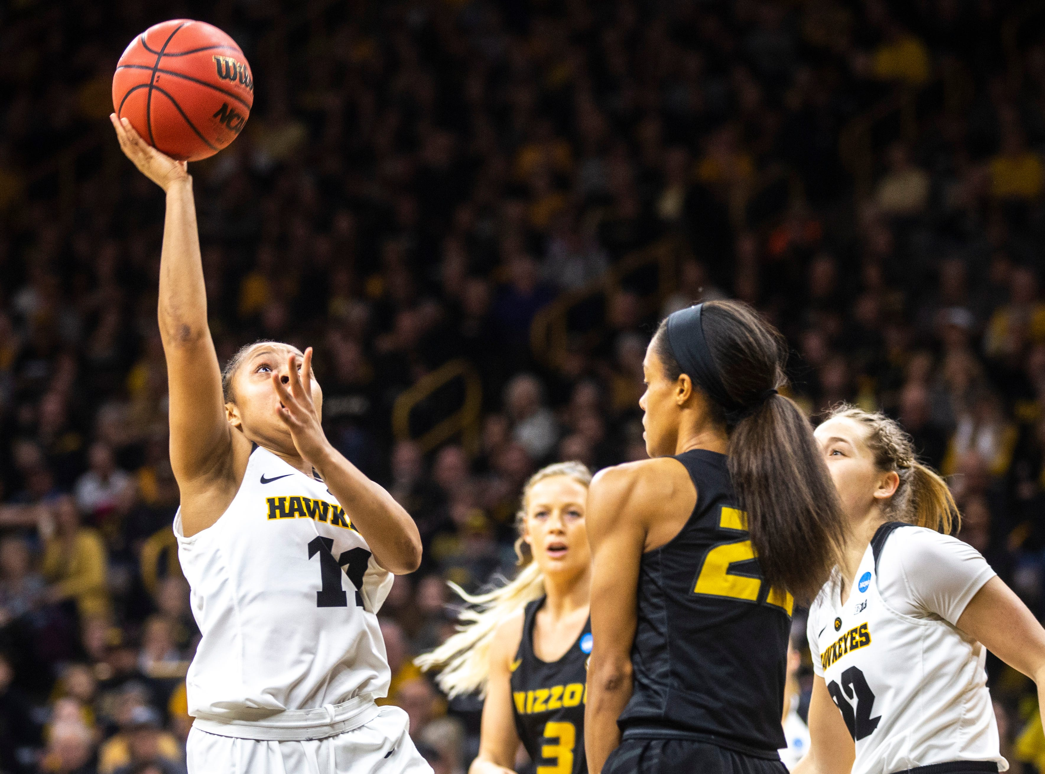 Iowa guard Tania Davis (11) shoots a basket against Missouri guard Jordan Roundtree (22) during a NCAA women's basketball tournament second-round game, Sunday, March 24, 2019, at Carver-Hawkeye Arena in Iowa City, Iowa.