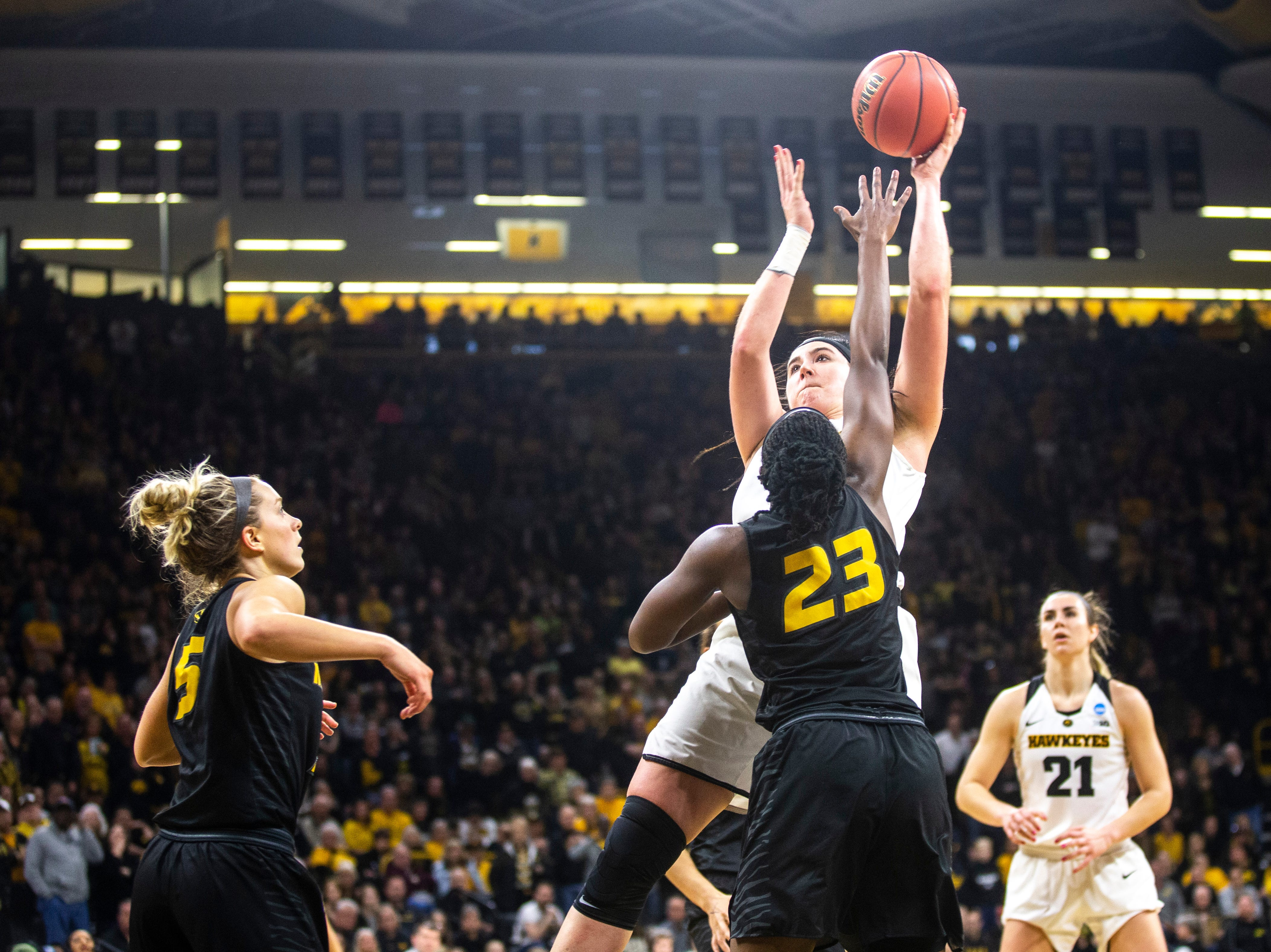 Iowa center Megan Gustafson shoots a basket against Missouri guard Amber Smith (23) while Missouri guard Lauren Aldridge (5) defends during a NCAA women's basketball tournament second-round game, Sunday, March 24, 2019, at Carver-Hawkeye Arena in Iowa City, Iowa.