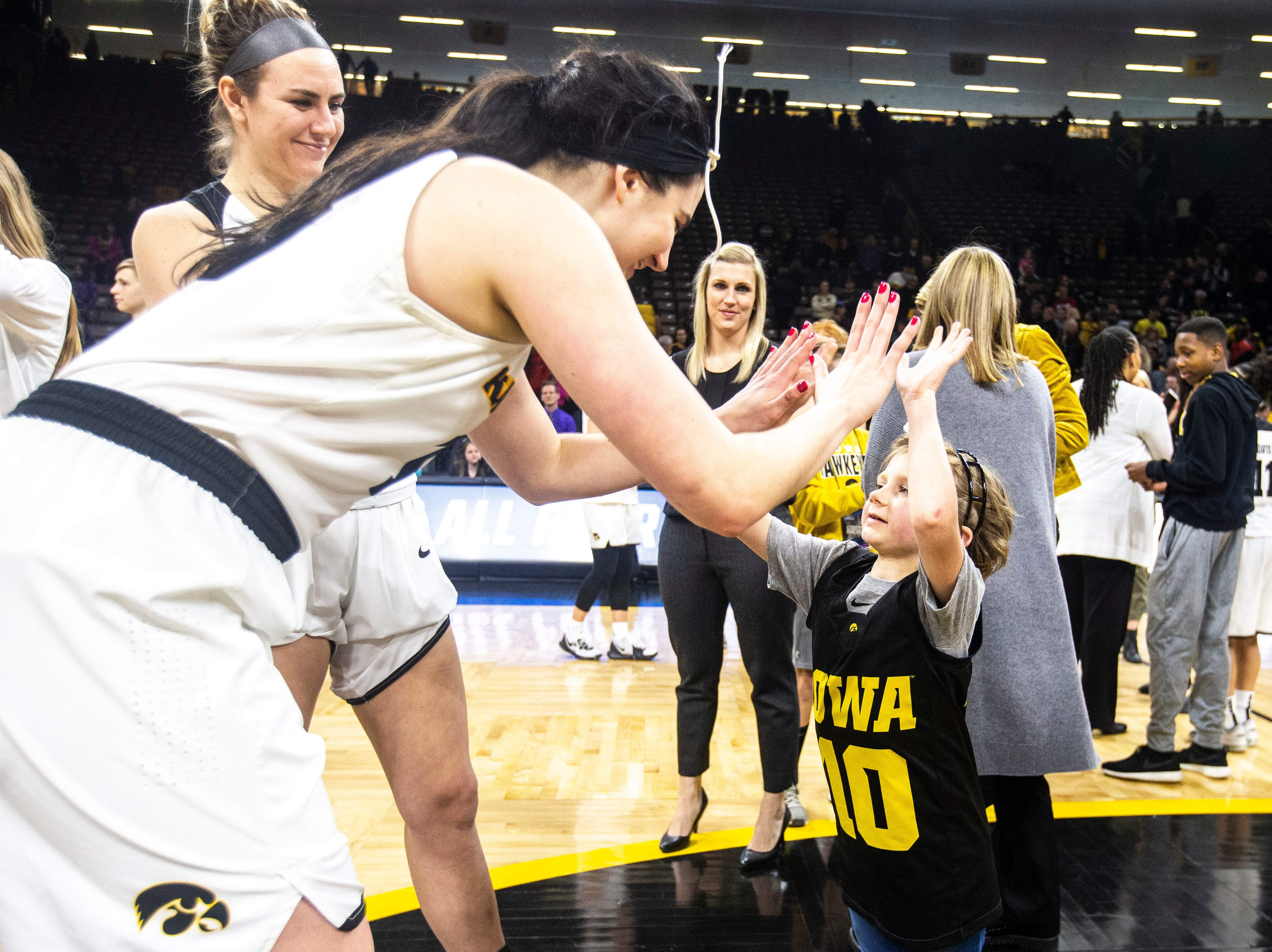 Iowa center Megan Gustafson (10) high-fives Harper Stribe, 6, after a NCAA women's basketball tournament second-round game, Sunday, March 24, 2019, at Carver-Hawkeye Arena in Iowa City, Iowa.