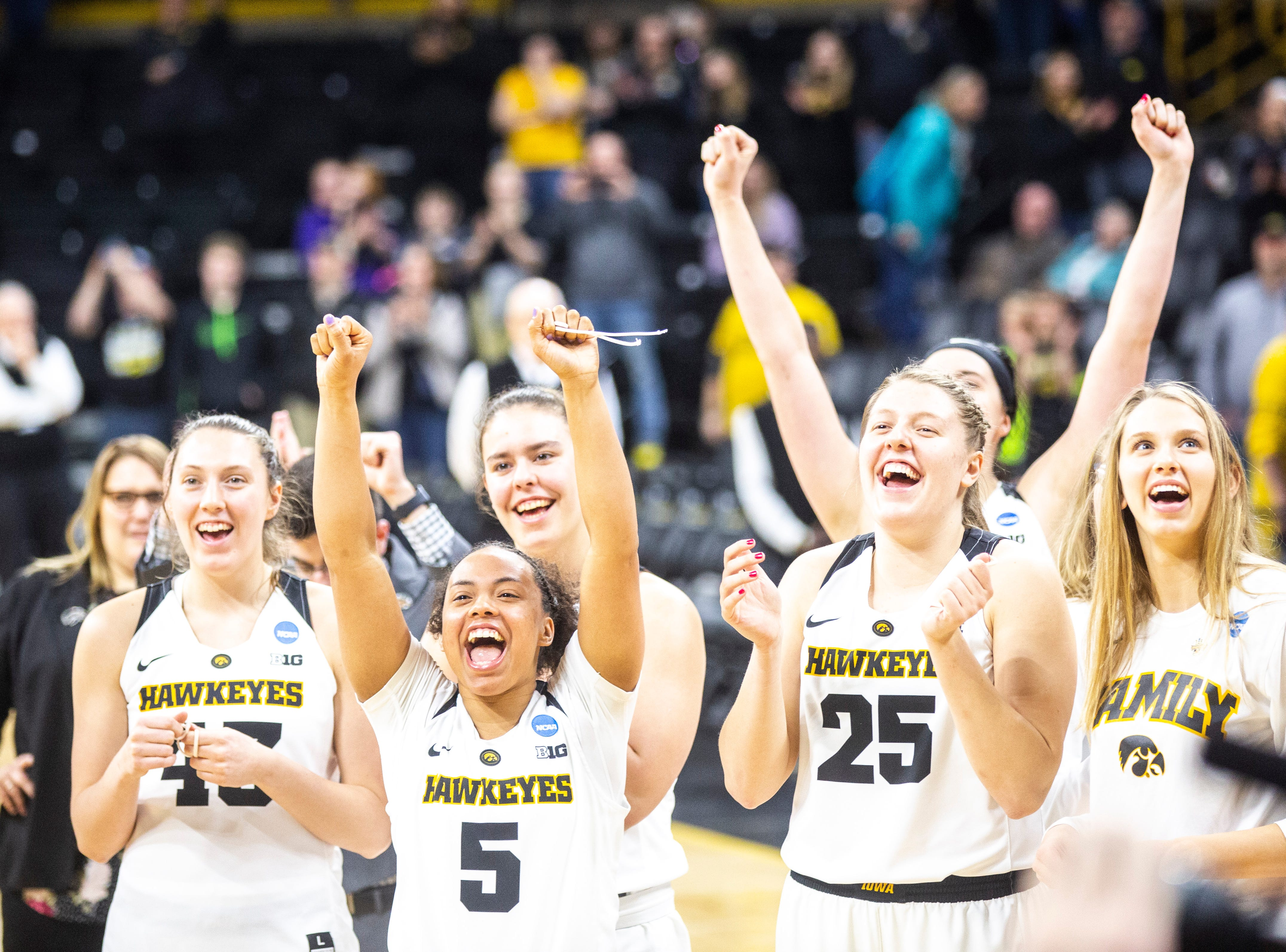 Iowa Hawkeyes cheer while teammates cut down the nets on the court after a NCAA women's basketball tournament second-round game, Sunday, March 24, 2019, at Carver-Hawkeye Arena in Iowa City, Iowa.