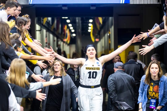 Iowa center Megan Gustafson (10) high-fives fans while heading to the floor to cut down the nets on the court after a NCAA women's basketball tournament second-round game, Sunday, March 24, 2019, at Carver-Hawkeye Arena in Iowa City, Iowa.