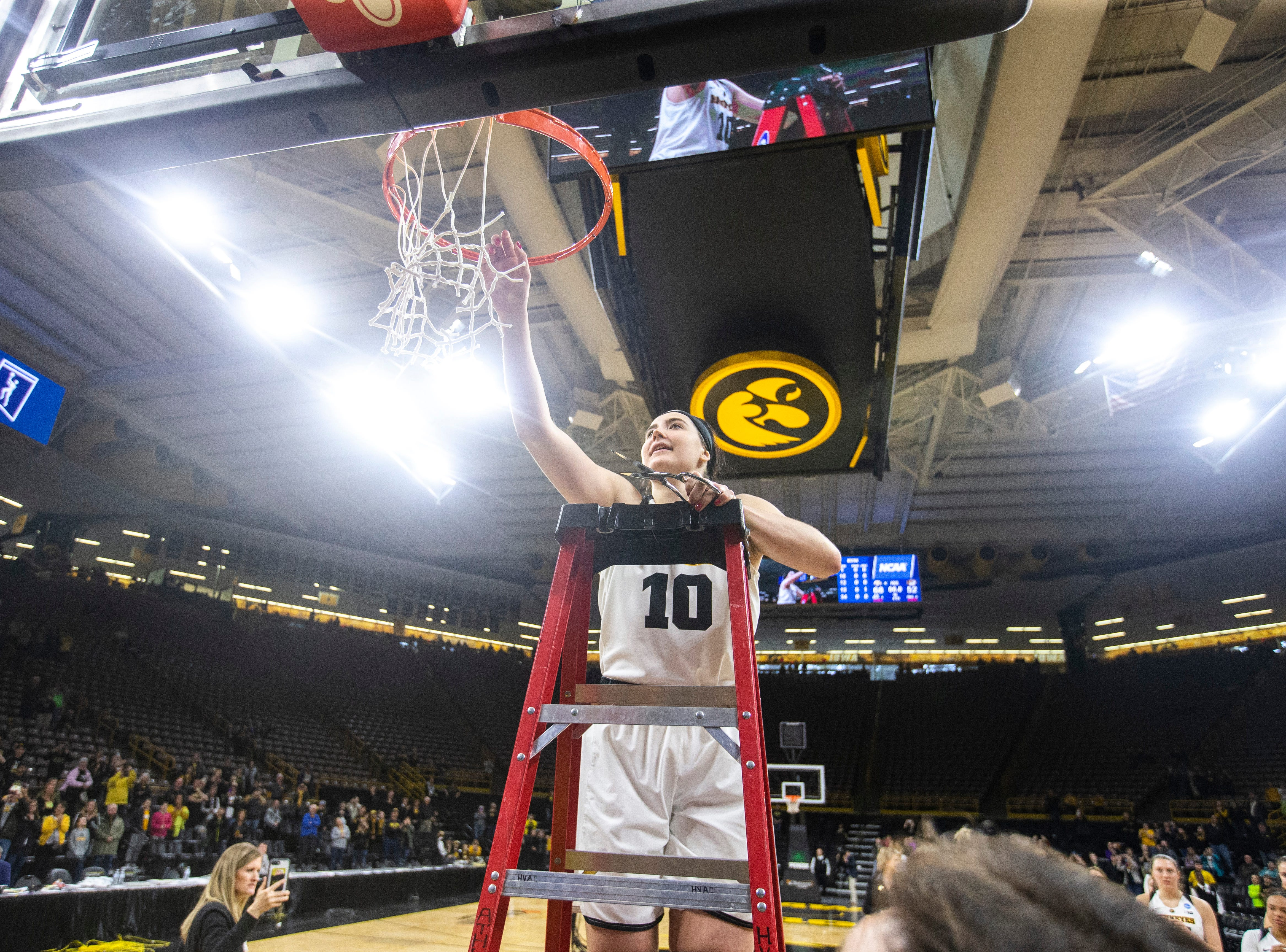 Iowa center Megan Gustafson (10) cuts down a piece of the net after a NCAA women's basketball tournament second-round game, Sunday, March 24, 2019, at Carver-Hawkeye Arena in Iowa City, Iowa.