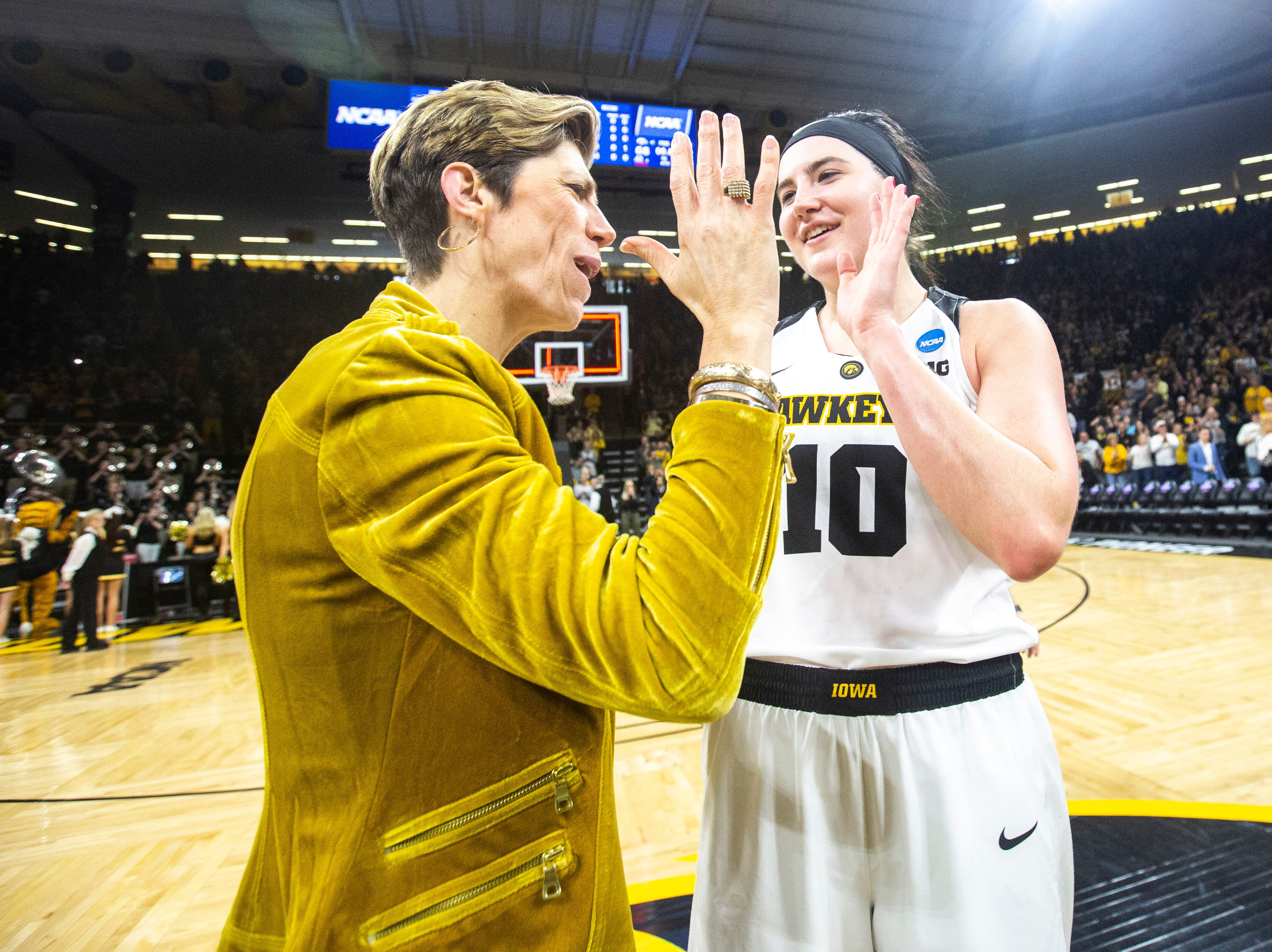 Iowa center Megan Gustafson (10) high-fives associate Jan Jensen after a NCAA women's basketball tournament second-round game, Sunday, March 24, 2019, at Carver-Hawkeye Arena in Iowa City, Iowa.
