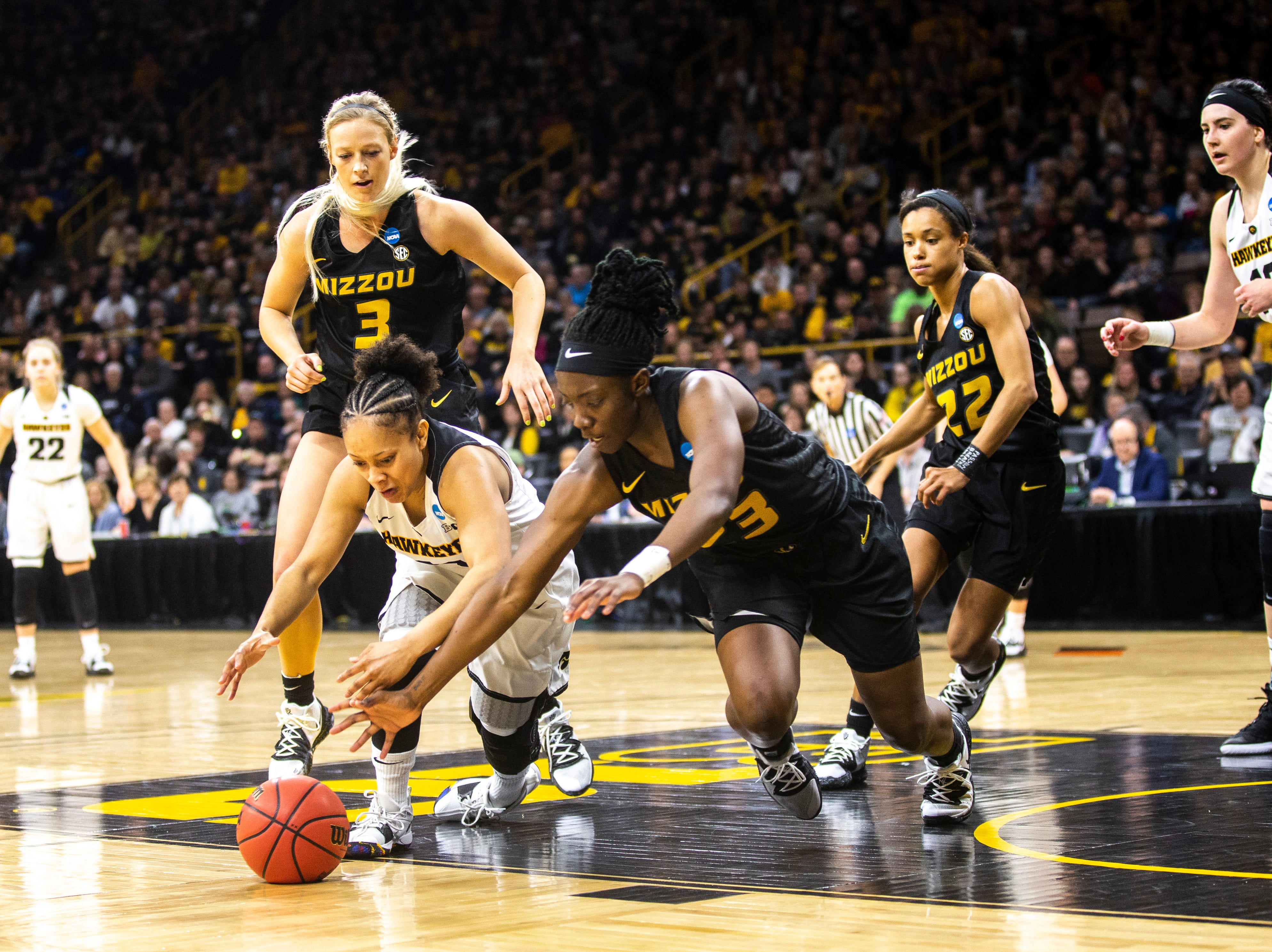Iowa guard Tania Davis (11) dives for a loose ball against Missouri guard Amber Smith (23) during a NCAA women's basketball tournament second-round game, Sunday, March 24, 2019, at Carver-Hawkeye Arena in Iowa City, Iowa.