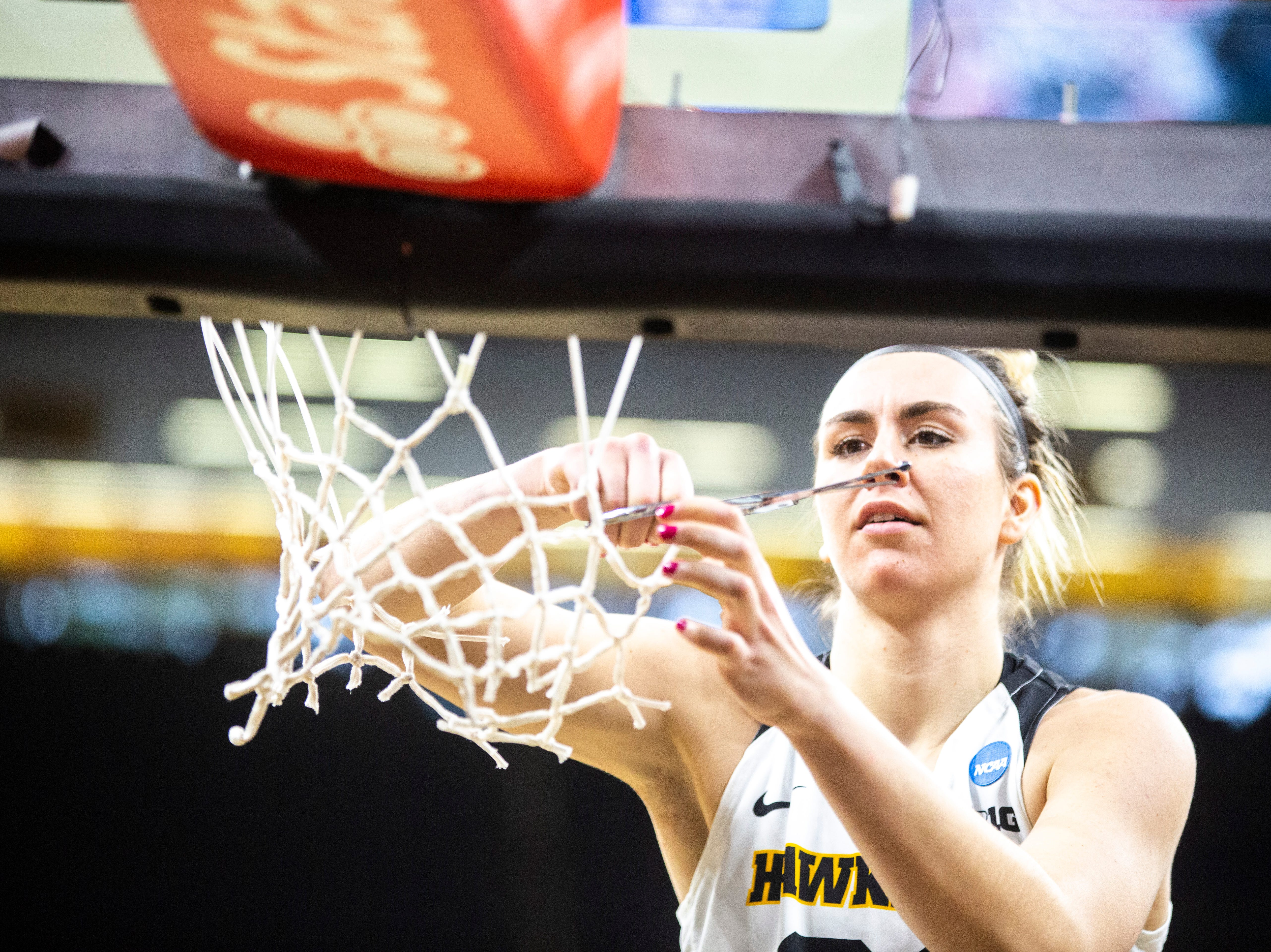 Iowa forward Hannah Stewart (21) cuts down the nets on the court after a NCAA women's basketball tournament second-round game, Sunday, March 24, 2019, at Carver-Hawkeye Arena in Iowa City, Iowa.