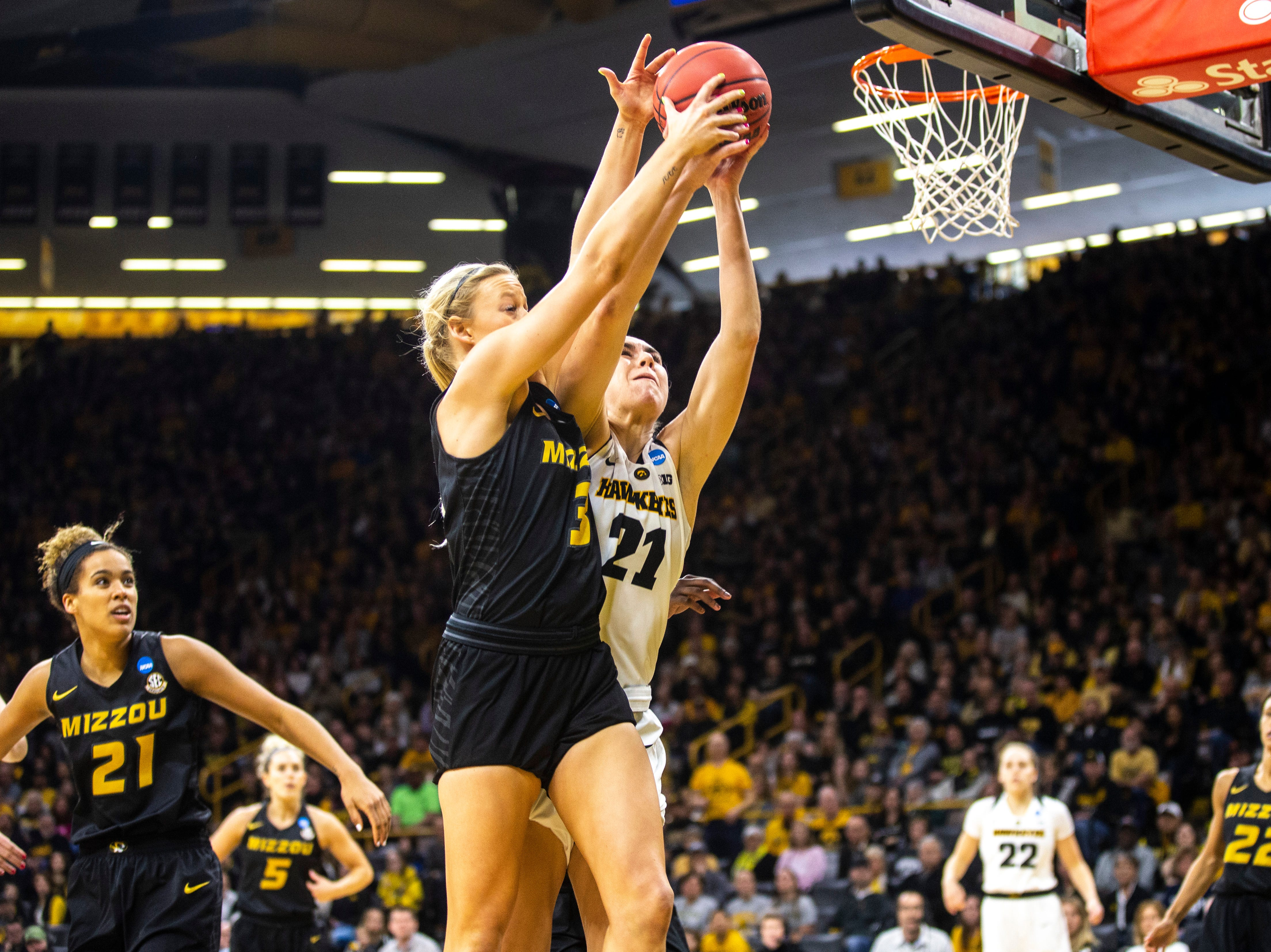Iowa forward Hannah Stewart (21) goes for a rebound against Missouri guard Sophie Cunningham (3) during a NCAA women's basketball tournament second-round game, Sunday, March 24, 2019, at Carver-Hawkeye Arena in Iowa City, Iowa.