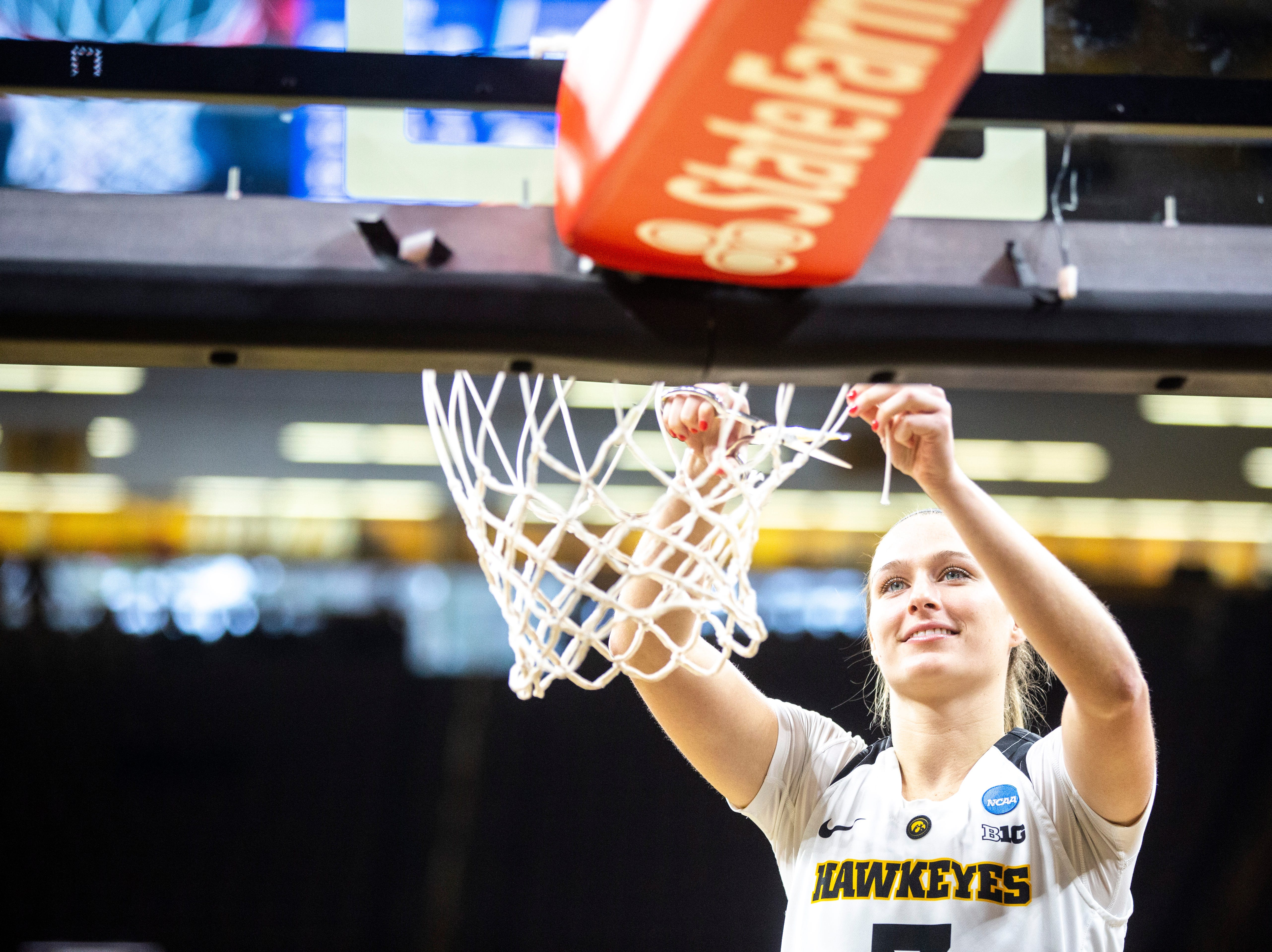 Iowa guard Makenzie Meyer (3) cuts down the nets on the court after a NCAA women's basketball tournament second-round game, Sunday, March 24, 2019, at Carver-Hawkeye Arena in Iowa City, Iowa.