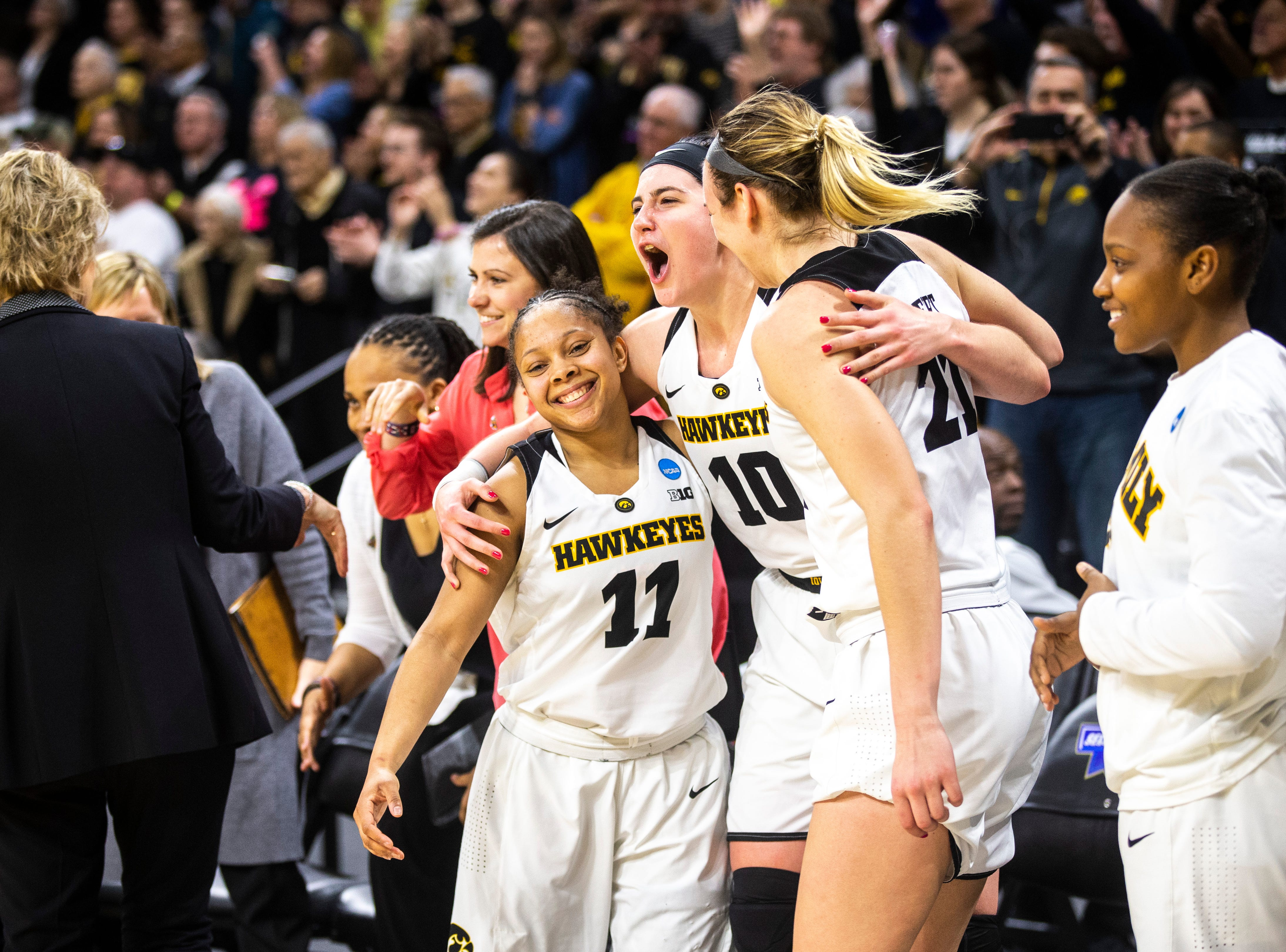 Iowa guard Tania Davis (11) celebrates with teammates Iowa center Megan Gustafson (10) and Iowa forward Hannah Stewart (21) during a NCAA women's basketball tournament second-round game, Sunday, March 24, 2019, at Carver-Hawkeye Arena in Iowa City, Iowa.