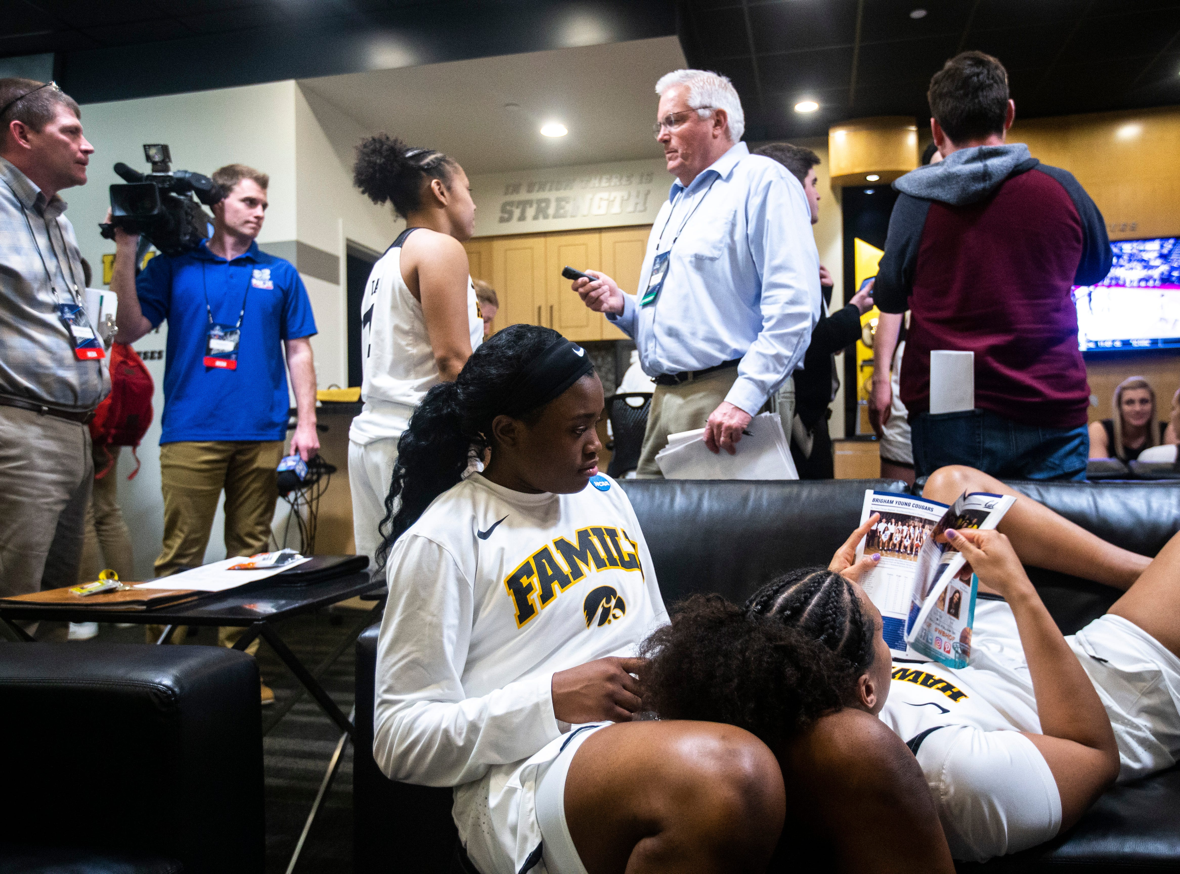 Iowa guard Alexis Sevillian reads a magazine with guard Tomi Taiwo, left, as reporters interview their teammates after a NCAA women's basketball tournament second-round game, Sunday, March 24, 2019, at Carver-Hawkeye Arena in Iowa City, Iowa.