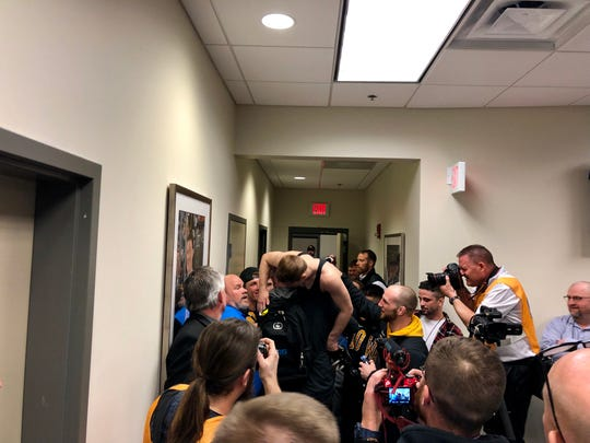 Iowa's Spencer Lee gets carried out of his post-match press conference by Sam Stoll while being surrounded by other members of the Iowa wrestling team.