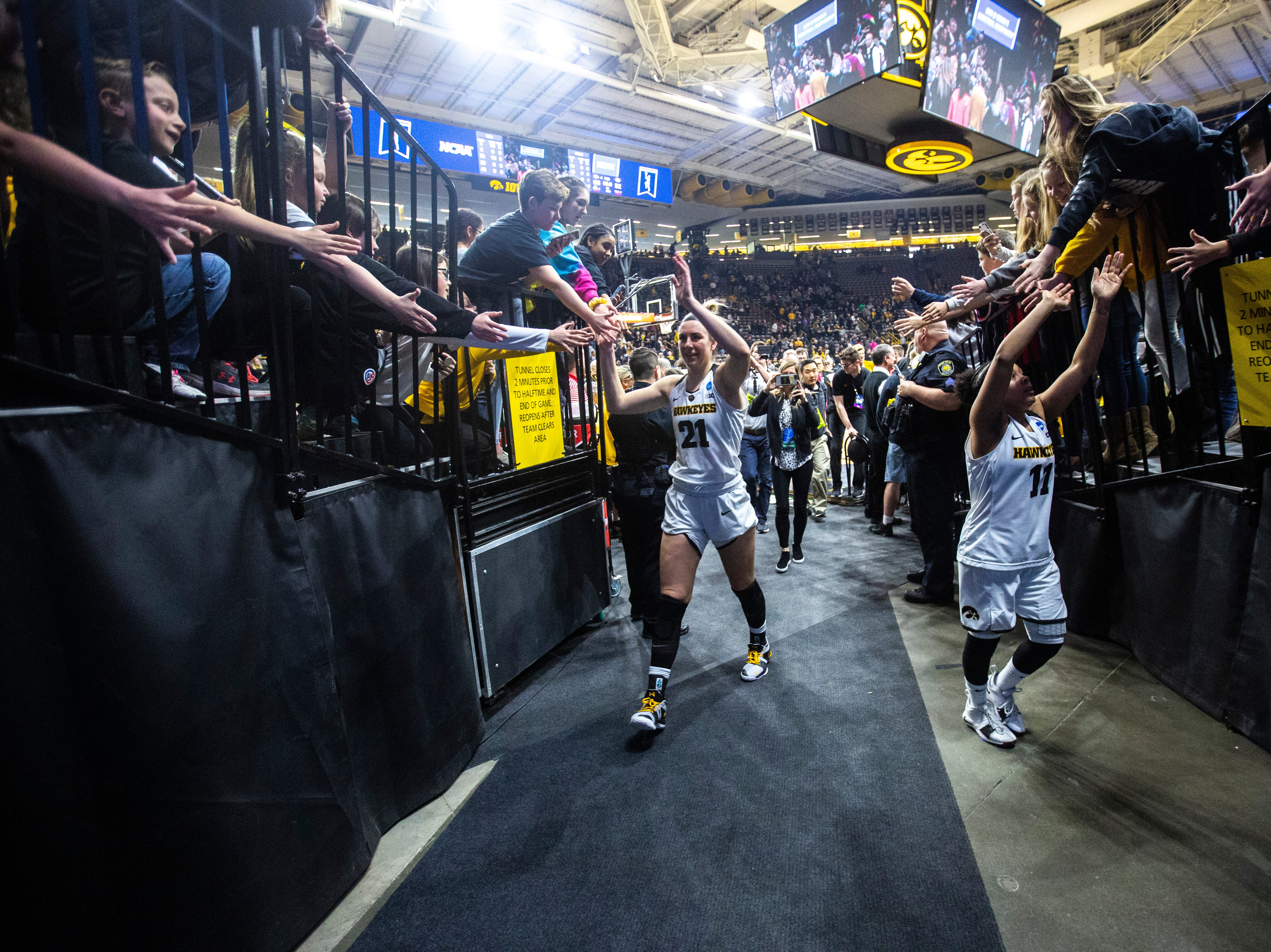 Iowa forward Hannah Stewart (21) and Iowa guard Tania Davis (11) high-five fans while leaving the court after a NCAA women's basketball tournament second-round game, Sunday, March 24, 2019, at Carver-Hawkeye Arena in Iowa City, Iowa.