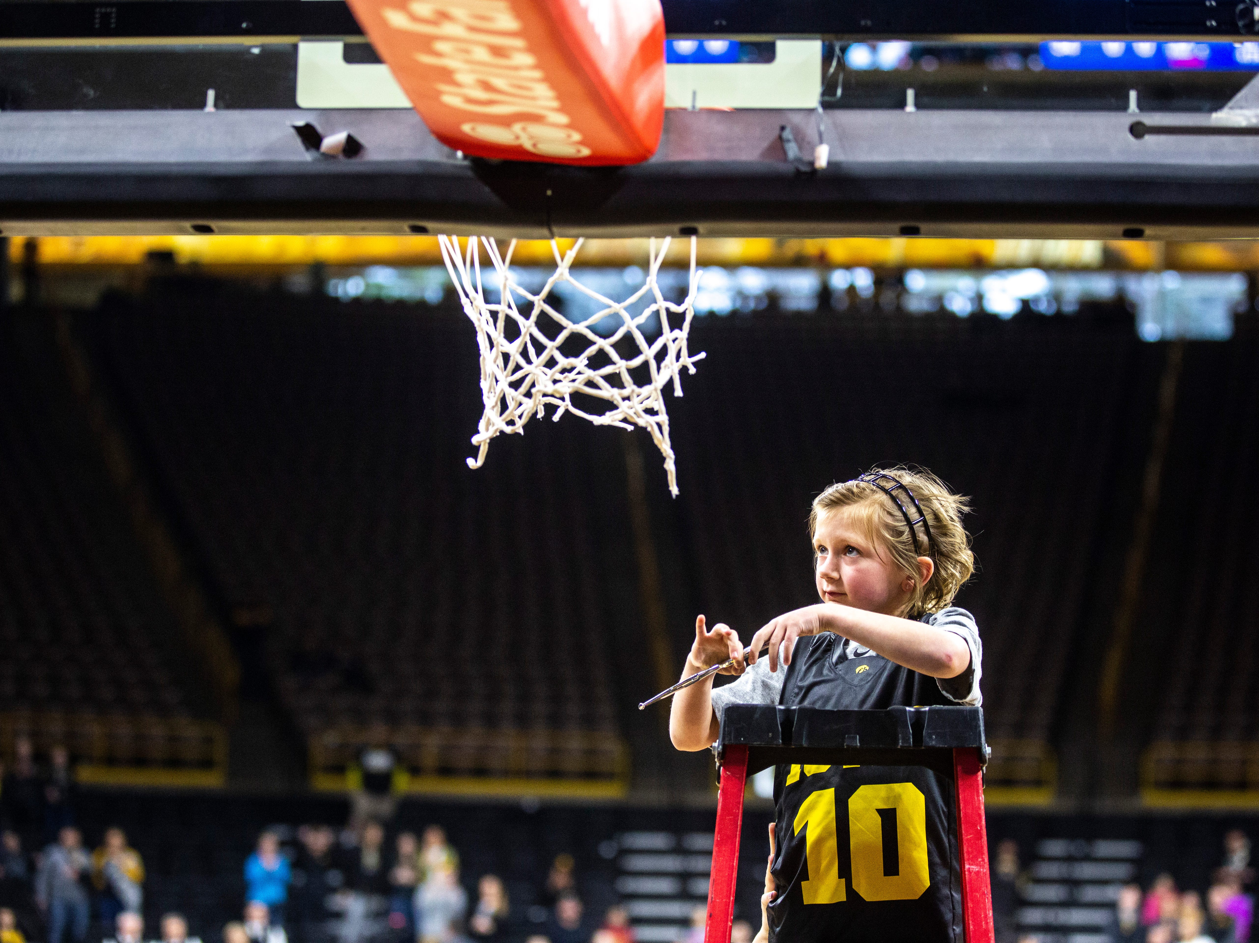 Harper Stribe, 6, cuts down the nets on the court after a NCAA women's basketball tournament second-round game, Sunday, March 24, 2019, at Carver-Hawkeye Arena in Iowa City, Iowa.