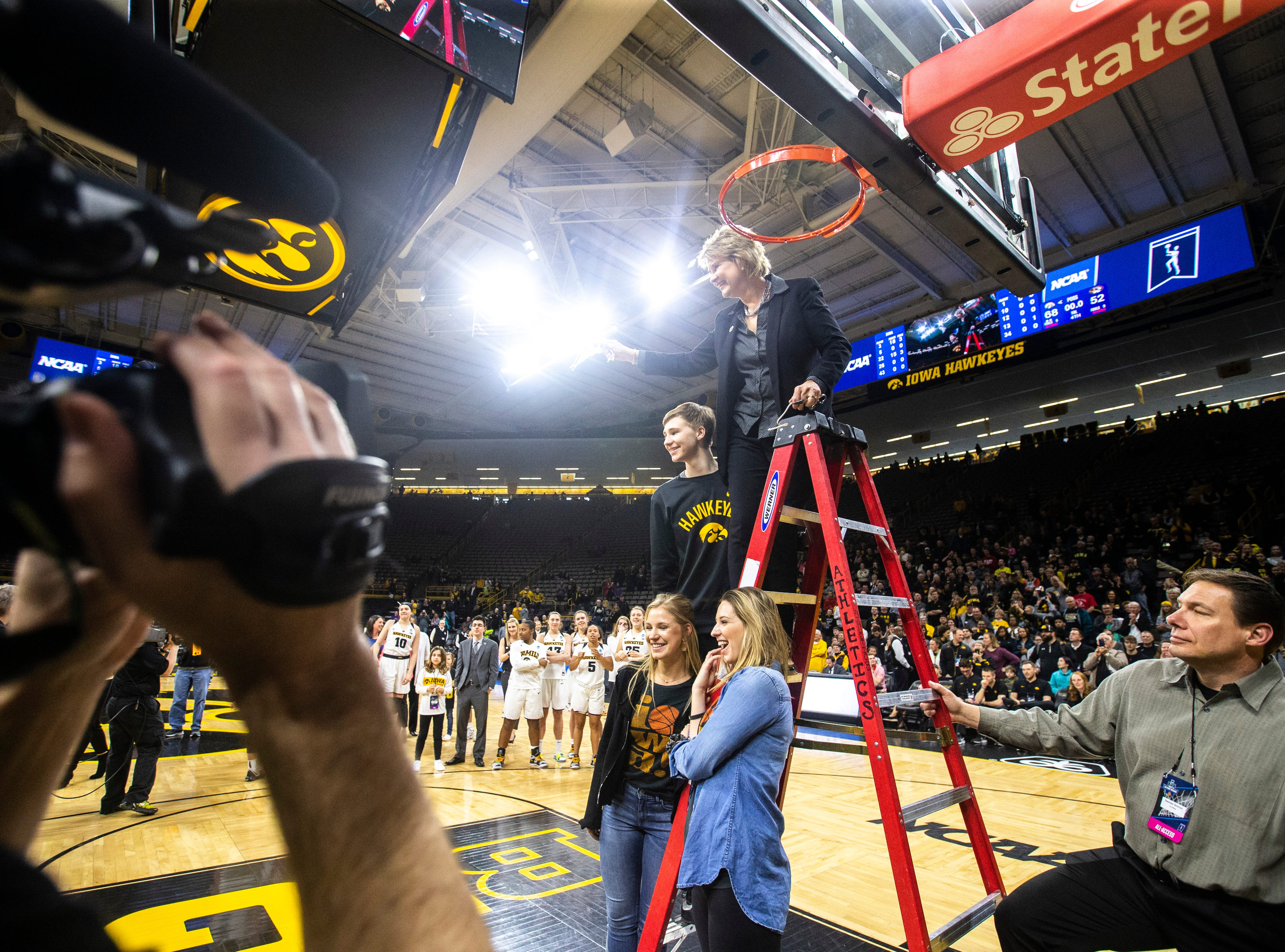 Iowa head coach Lisa Bluder poses for a photo with her children, Emma, David and Hannah after cutting down the nets on the court after a NCAA women's basketball tournament second-round game, Sunday, March 24, 2019, at Carver-Hawkeye Arena in Iowa City, Iowa.